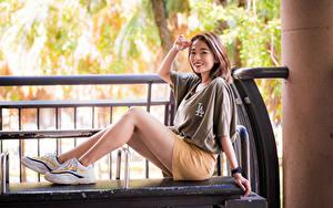 Fotos Asiaten Lächeln Sitzt Bein Sportschuhe Shorts T-Shirt Starren junge frau