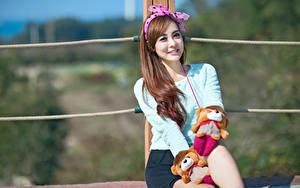 Bilder Asiatisches Spielzeuge Bokeh Schleife Blick Sitzend Lächeln Mädchens