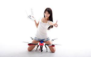 Fotos Asiaten UAV Quadrokopter Shorts Unterhemd Blick Weißer hintergrund Mädchens Luftfahrt