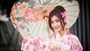 Bilder Asiaten Regenschirm Braune Haare Starren Lächeln junge frau