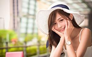 Fotos Asiatische Armbanduhr Unscharfer Hintergrund Der Hut Braunhaarige Blick Lächeln Hand