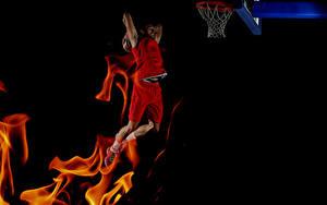 Bilder Basketball Mann Flamme Schwarzer Hintergrund Sprung sportliches
