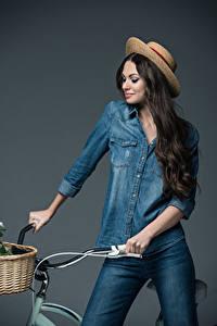 Fotos Fahrradlenker Grauer Hintergrund Der Hut Jeans Haar Lächeln Brünette junge Frauen
