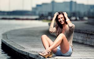 Fotos Bokeh Braune Haare Lächeln Sitzen Hand Shorts Bein junge Frauen