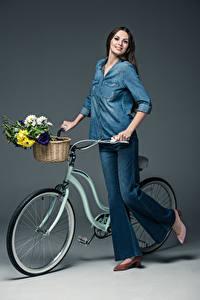 Bilder Sträuße Grauer Hintergrund Braune Haare Lächeln Fahrrad Jeans Hemd Weidenkorb Mädchens