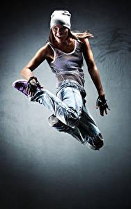 Bilder Braunhaarige Tanz Sprung Freude Mütze Jeans Hand junge frau