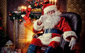Bilder Kerzen Flamme Sessel Weihnachtsmann Sitzt Mütze Barthaar Brille Geschenke