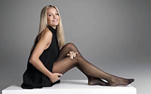 Fotos Grauer Hintergrund Blond Mädchen Lächeln Kleid Hand Sitzend Bein Strumpfhose Model Caroline Fleming Mädchens