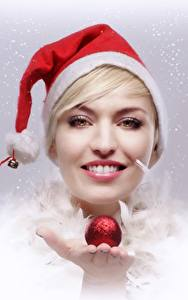 Bilder Neujahr Blondine Mütze Lächeln Starren Hand Kugeln junge Frauen