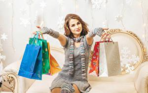Bilder Neujahr Braune Haare Sitzt Geschenke Lächeln Hand Tüte Kleid Einkaufen Mädchens