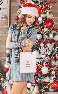 Hintergrundbilder Neujahr Braunhaarige Mütze Tannenbaum Geschenke Kleid Kugeln Mädchens