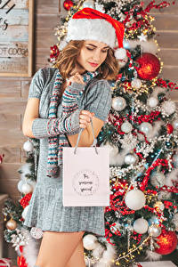 Hintergrundbilder Neujahr Braunhaarige Mütze Tannenbaum Geschenke Kleid Kugeln