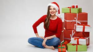 Fotos Neujahr Braune Haare Mütze Sitzt Starren Lächeln Geschenke Grauer Hintergrund junge frau