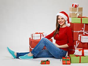Fotos Neujahr Grauer Hintergrund Braunhaarige Geschenke Blick Lächeln Mütze Jeans Sitzend Mädchens