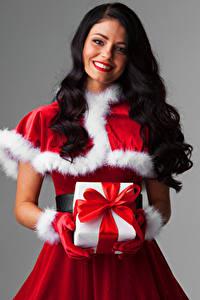 Bilder Neujahr Grauer Hintergrund Brünette Lächeln Geschenke Uniform Haar Schleife Mädchens