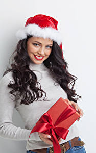 Hintergrundbilder Neujahr Grauer Hintergrund Brünette Lächeln Mütze Geschenke Mädchens