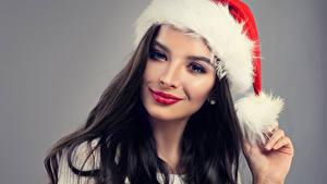 Bureaubladachtergronden Nieuwjaar Grijze achtergrond Brunette meisje Winter Hoed Kijkt Mooie jonge vrouw