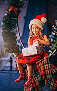 Bilder Neujahr Kleine Mädchen Sitzt Mütze Geschenke Ast Kinder