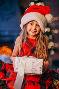 Fotos Neujahr Kleine Mädchen Lächeln Geschenke Mütze Blick kind