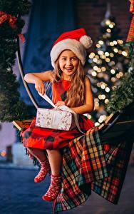 Bilder Neujahr Kleine Mädchen Lächeln Mütze Sitzt Geschenke kind