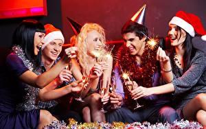 Bilder Neujahr Mann Mütze Blondine Sitzend Lacht Freude Hand Wunderkerze Weinglas junge frau