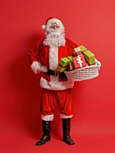 Bilder Neujahr Roter Hintergrund Weihnachtsmann Uniform Weidenkorb Geschenke Barthaar