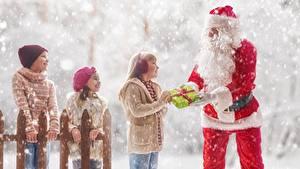 Bilder Neujahr Winter Schnee Weihnachtsmann Kleine Mädchen Geschenke Mütze Zaun Kinder