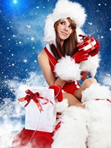Bilder Neujahr Mütze Braunhaarige Sitzend Geschenke Mädchens