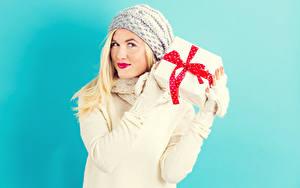 Fotos Farbigen hintergrund Blond Mädchen Starren Geschenke Mütze Rote Lippen