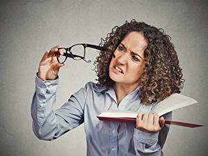 Fotos Lockige Grauer Hintergrund Braunhaarige Brille Buch Hand Missfallen junge frau
