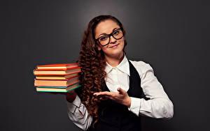 Hintergrundbilder Lockige Grauer Hintergrund Braunhaarige Lächeln Buch Hand Brille Starren junge Frauen