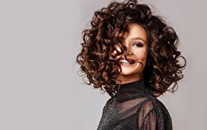 Fotos Locken Grauer Hintergrund Model Schminke Frisuren Braune Haare Lächeln Schöne junge frau
