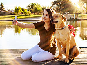 Fotos Hund Braunhaarige Selfie Sitzen Lächeln Smartphone Labrador Retriever junge frau Tiere