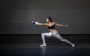 Bilder Posiert Degen Hand Bein Trainieren Braunhaarige Fencing junge Frauen Sport