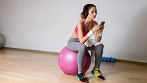 Fotos Fitness Ball Sitzt Sportschuhe Kopfhörer Smartphones sportliches Mädchens