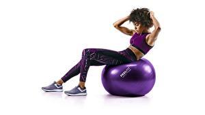 Bilder Fitness Ball Sitzt Körperliche Aktivität Weißer hintergrund junge Frauen Sport