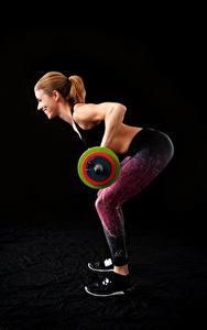 Fotos Fitness Schwarzer Hintergrund Braune Haare Lächeln Trainieren Hantelstange Sportliches Mädchens