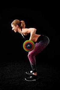 Desktop hintergrundbilder Fitness Schwarzer Hintergrund Braune Haare Lächeln Trainieren Hantelstange Sportliches junge frau Mädchens