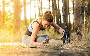 Fotos Fitness Braune Haare Sitzen Dehnübung Unscharfer Hintergrund junge frau