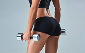 Hintergrundbilder Fitness Großansicht Hantel Hand Gesäß Grauer Hintergrund Shorts hips sportliches Mädchens