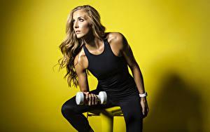 Bilder Fitness Farbigen hintergrund Sitzend Braune Haare Starren Unterhemd Hand Hanteln junge frau