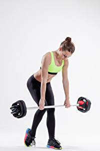 Fotos Fitness Grauer Hintergrund Braune Haare Körperliche Aktivität Hantelstange Mädchens Sport