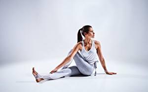 Bilder Fitness Grauer Hintergrund Sitzen Dehnübung Hand Bein Posiert junge Frauen
