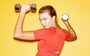 Hintergrundbilder Fitness Karlie Kloss Farbigen hintergrund Braune Haare Blick Hand Hantel Prominente Mädchens