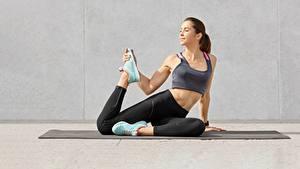 Bilder Fitness Bein Dehnübungen Sportschuhe Unterhemd sportliches Mädchens