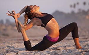 Bilder Fitness Sand Pose Braunhaarige Hand Bein Dehnübungen Mädchens