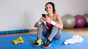 Bilder Fitness Sitzen Turnschuh Unterhemd Smartphones Kopfhörer Hanteln sportliches Mädchens