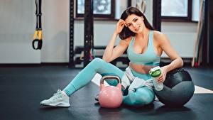 Bilder Fitness Sitzend Bein Turnschuh Kugelhantel Blick sportliches Mädchens