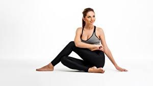 Fotos Fitness Sitzen Bein Unterhemd Lächeln Starren Weißer hintergrund Sport Mädchens