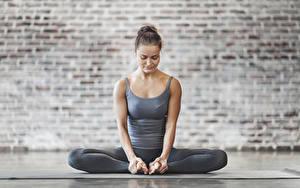 Bilder Fitness Sitzt Dehnübungen Braunhaarige Hand Bein Joga junge frau